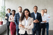 Successful Businesswoman Standing In Front Of Business Team In Office
