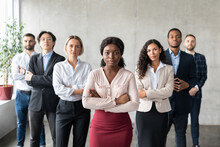 Determined Black Businesswoman Standing In Front Of Employees In Office