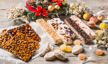 Various Christmas Desserts As Different Nougats With Almonds, Nuts, Peanuts, Candied Fruits, Marzipan Fruits And Cookies. Traditional Christmas Sweets.