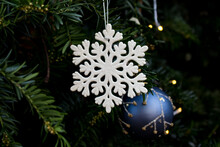 White Snowflake Ornament With Blue Christmas Tree Ball In Yew Branch