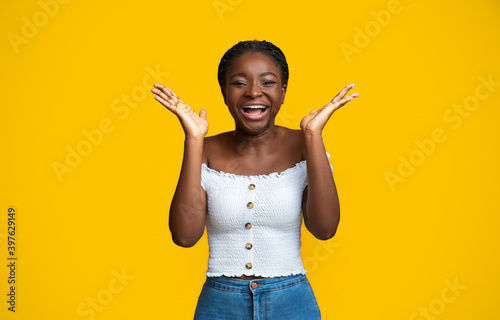 Photo Cheerful African American Woman Laughing And Raising Hands In Excitement, Yellow