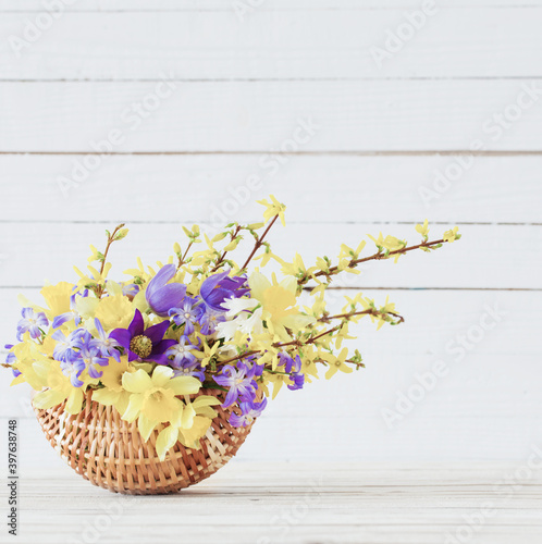Fotografia, Obraz spring flowers in basket on white wooden background