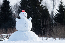 A Giant Snowman With A Red Bucket As A Hat In Northern European Garden During Winter Time.
