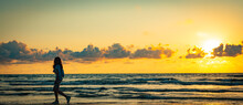 Lone Girl On Sunset Beach