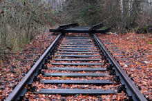 The End Of A Railway Line Blocked With Railroad Crossties And Rails In Autumn Covered With Fallen Leaves - Stockphoto