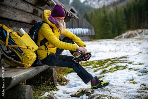Fototapeta Woman hiker in a yellow down jacket puts yellow crampons on her shoes before going to the mountains