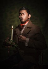 This Image Is A Painterly Portrait Of A Handsome Asian Man, Holding An Antique Burning Candle And Looking At The Camera While Posing In Sophisticated Attire.