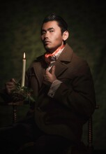 This Image Is A Painterly Style Victorian Portrait Of A A Well Dressed Asian Man, Holding An Antique Burning Candle And Fixing His Suit As He Looks Towards The Viewer.