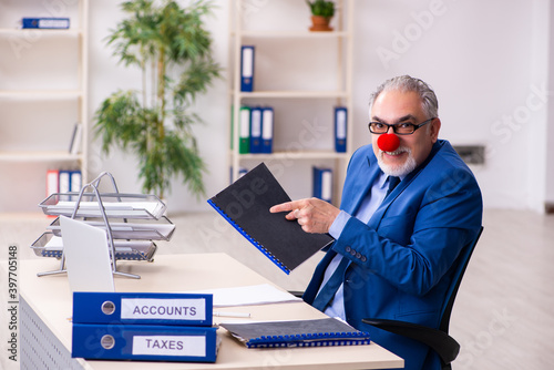 Obraz na plátne Old businessman clown working in the office