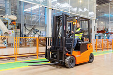 Storehouse Employee In Uniform Working On Forklift In Modern Automatic Warehouse. Boxes Are On The Shelves Of The Warehouse. Warehousing, Machinery Concept. Logistics In Stock.