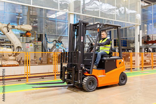 Fotografía Storehouse employee in uniform working on forklift in modern automatic warehouse