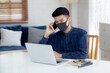Young asian business man in face mask talking smartphone and work on laptop computer for protect covid-19, businessman quarantine work from home with notebook, social distancing and stay home.