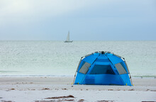 Early Morning Time Camping On The Shoreline Of A Tropical Beach In A Tent With A Sailboat Sailing By On The Calm Ocean In The Distance.