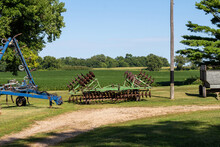 Landscape View Of Vintage Farm Implements, Including A Sprayer, Disc Cultivator, And A Grain Trailer