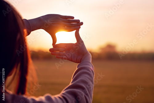 Tablou Canvas Future planning concept, Close up of woman hands making frame gesture with sunset, Female capturing the sunrise
