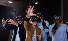 Portrait Of Group Of Young Adult People With Virtual Reality Goggles Gesturing Standing In Dark Room