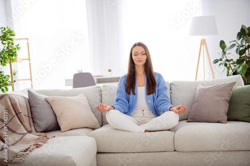 Fototapeta Portrait of pretty dreamy peaceful girl sitting on divan meditating free time in