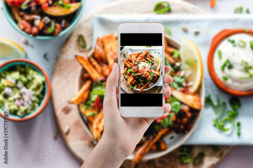 Hand taking a photo of Healthy food with smartphone. Woman using phone mobile apps make digital picture on screen of diet nutrition vegan fruit granola seed on table, top view