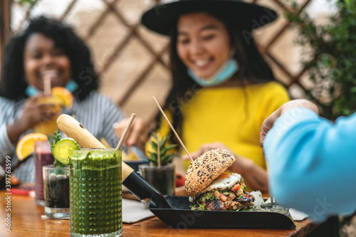 Fotografía Multiracial friends having healthy lunch in coffee brunch bar during corona viru