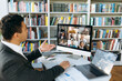 Online video conference. Successful young adult businessman communicate with  business colleagues by video call using computer discussing about financial graphs and strategy