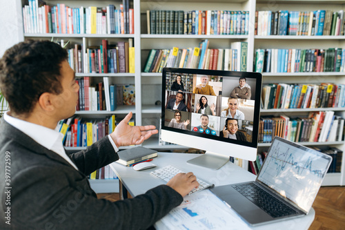 Fototapeta Online video conference. Successful young adult businessman communicate with  business colleagues by video call using computer discussing about financial graphs and strategy obraz
