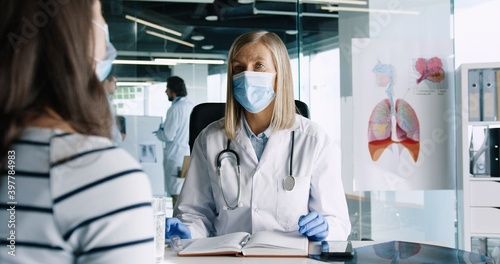 Fototapety, obrazy: Portrait of senior female physician in medical mask sitting in cabinet in clinic and talking on consultation with young Caucasian woman patient. Male doctors talking on background. Clinic concept