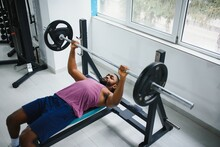 Weight Lifter At The Bench Press Lifting A Barbell On An Bench