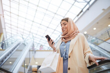 Low Angle Portrait Of Smiling Middle-Eastern Woman Looking At Smartphone Screen While Standing On Escalator In Shopping Mall, Copy Space