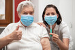 elderly senior woman and a female nurse show that they are in favor of a vaccination