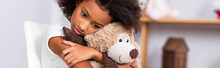 Depressed African American Girl Hugging Teddy Bear With Blurred Office On Background, Banner