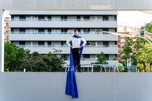 Businessman Wearing Superhero Cape Standing On A Wall In The City