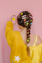 Teenage Girl With Various Hair Pins In Her Braid, Holding Smartphone With Smiling Emoji, Rear View