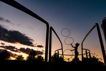 Silhouette Sporty Woman Juggling Plastic Hoops Against Sky During Sunset