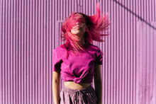 Young Woman With Dyed Red Hair Dancing In Front Of Purple Wall In The City