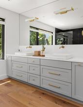 Bathroom In Luxury Home With Double Vanity, Large Mirror, Sinks, Cabinets, And Hardwood Floor