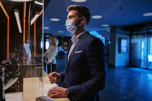 Fotografie, Obraz A middle-aged man in formal wear with a face mask standing on the reception of a fancy hotel and checking in