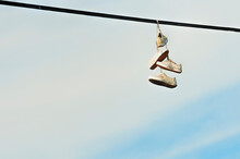 Two Pairs Of Shoes Hanging From Powerlines
