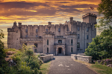 Front entrance of Dunvegan Castle on the Isle of Skye, Scottish Highlands at Loch of Dunvegan, in a dramatic sunset, Scotland