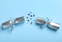 Open Silver Christmas Cracker With Shiny Confetti On Light Blue Background, Top View