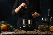 The Chef Pours Ground Ginger Into Pan For Preparing Mulled Wine On Rustic Wooden Table With Festive Composition Background. Backstage Of Cooking Hot Drink With Fragrant Spices.