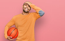 Hispanic Adult Man Holding Basketball Ball Stressed And Frustrated With Hand On Head, Surprised And Angry Face