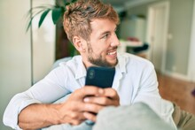 Handsome Caucasian Man Smiling Happy Sitting On The Sofa At Home Using Smartphone