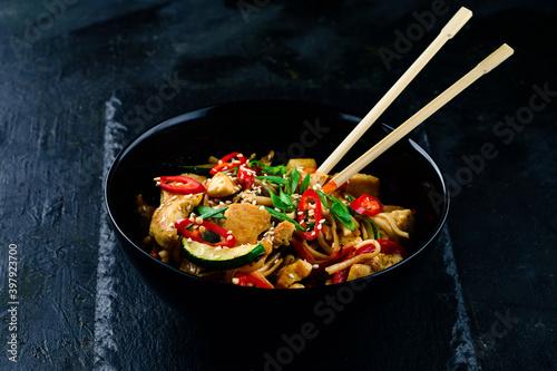 Fotografija Udon stir fry noodles with chicken and vegetables on black background
