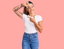 Young Hispanic Woman With Tattoo Wearing Casual White Tshirt Smiling Making Frame With Hands And Fingers With Happy Face. Creativity And Photography Concept.