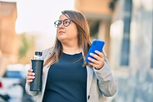 Young Plus Size Businesswoman Using Smartphone Drinking Bottle Of Water At The City.