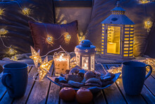 Cozy Sitting Area With Coffee And Cookies On A Balcony, Decorated For Winter With Lanterns, Candles, Woolen Blankets And Fairy Lights