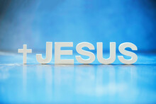 Name JESUS Made With Cement Letters On Blue Light Marble Background. Copy Space. Biblical, Spiritual Or Christian Reminder
