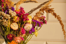 Multicolored Dried Flowers In The Soft Sunlight With A Shadow On The White Tile. The Decoration Of The House Or Apartment. Bouquet Of Potpourri
