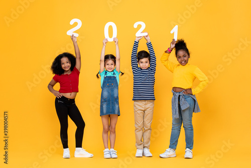 Fototapeta Cute mixed race kids smiling and holding 2021 numbers isolated on yellow background for new year concepts obraz