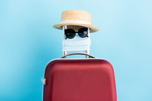 Sunglasses, Medical Mask And Straw Hat On Red Luggage On Blue